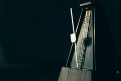 Vintage metronome, on a dark background. Color shot of a vintage metronome, on a black background Stock Image