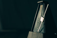Vintage metronome, on a dark background. Royalty Free Stock Photos