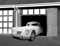 Vintage mg sports car in driveway. Photo of a vintage mg sports car coming out of garage ready for a cruise around town royalty free stock photography