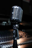 Vintage microphone 2. A vintage microphone with the mixer background royalty free stock image