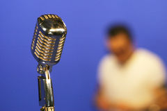 Vintage microphone. Old-style chrome microphone with a singer on the background on a blue box Stock Photo