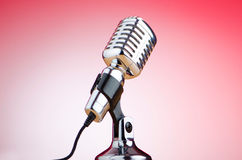 Vintage microphone against red background Stock Images