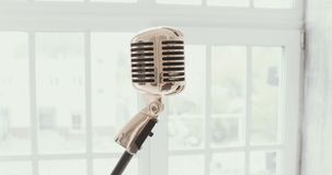 Vintage microphone against a window. white background . Slow motion. stock footage
