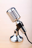 Vintage microphone against wooden background Royalty Free Stock Images