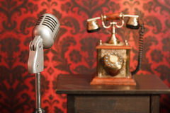 Vintage microphone in background an phone Stock Images