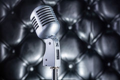Vintage microphone on black leather background. Grey vintage microphone on black leather background Stock Photos