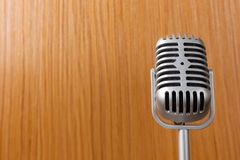 The vintage microphone close up image on wood background. Vintage microphone close up image on wood background stock photos