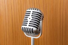 The vintage microphone close up image on wood background. Vintage microphone close up image on wood background stock image