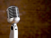 Vintage Microphone in front of blurred background. A silver vintage microphone in front of a blurred red brick wall with copy space royalty free stock photo