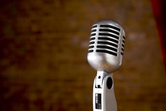 Vintage Microphone in front of blurred background. A silver vintage microphone in front of a blurred red brick wall with copy spaceThis is the 4000000th image stock image