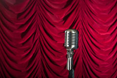 Vintage microphone in front of red curtain. Backdrop royalty free stock photo