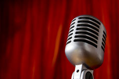 Vintage Microphone in front of red Curtain. A silver vintage microphone in front of a red stage curtain with copy space stock images