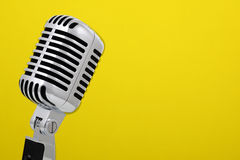 Vintage microphone isolated on yellow stock photos