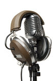 Vintage Microphone with modern headphones. Vintage microphone on stand with a modern pair of headphones on it royalty free stock photo