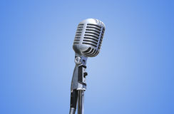 Vintage Microphone over blue background Royalty Free Stock Image