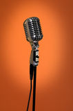 Vintage Microphone Over Orange Background Royalty Free Stock Photos