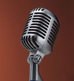Vintage microphone on red. Background Royalty Free Stock Images