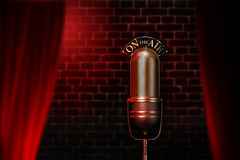 Vintage microphone on red cabaret stage. Old mic on air behind a curtain with red lights and wall on the background Royalty Free Stock Photos