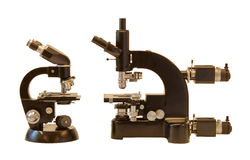 Vintage Microscope family, side view. Black vintage microscope family (isolated), basic and advanced model side by side royalty free stock photography