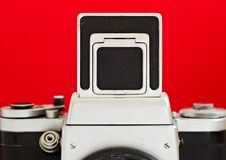 Vintage camera. This is Pentacon Six medium format camera, front view on a plain red background. The viewfinder is opened from top royalty free stock images