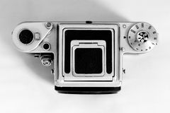 Vintage middle format camera with shadow. This is Pentacon Six middle format camera, top view on a plain white background. The viewfinder is closed and the royalty free stock photos