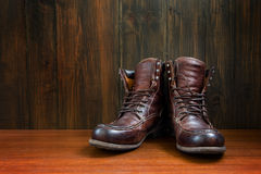 Vintage military boots on wooden background Royalty Free Stock Photos