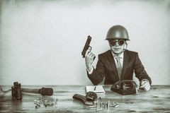 Vintage military businessman sitting at office desk with hand gun Stock Images