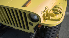 Vintage military vehicle. A close up front view of a vintage military vehicle painted yellow stock photography