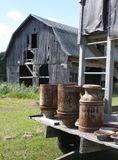 Vintage Milk Cans on a hay wagon. With an old barn in the background stock image