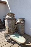 Vintage milk churns with cart Royalty Free Stock Photography