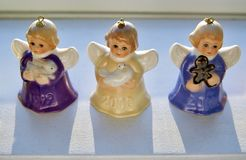 Vintage, Miniature and Colourful Angel Bells are Rear Life by Heavenly Sunshine on a Shelve during Christmas Season. Each precious angelic winged ornament is Stock Images