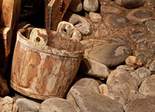 Vintage Mining Bucket and Dry River. A vintage wooden mining bucket sits in a dry riverbed of weathered stones royalty free stock images