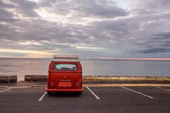 Vintage minivan on empty parking lot. Vintage minivan on empty parking lot at the beach at sunset Royalty Free Stock Images