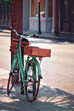 A vintage mint green bike parked in downtown Charleston, South Carolina. A vintage mint green bike with two wooden baskets parked in downtown Charleston, South Stock Image