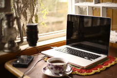 Vintage mix modern still life with laptop oil lamp, tea cup, lenses Stock Image