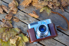 Vintage 35mm camera. Vintage 35mm Rangefinder camera on rustic table with autumn leaves Stock Photo