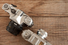 Vintage 35mm film cameras both lying over a dated wooden background Royalty Free Stock Photo