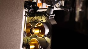 Vintage 35mm film running through a cinema projector in a movie theater