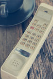 Vintage mobile phone with coffee cup Royalty Free Stock Photography