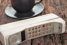 Vintage mobile phone with coffee cup Stock Images