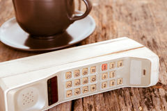 Vintage mobile phone with coffee cup Stock Photo