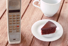 Vintage mobile phone with cup. Of coffee and chocolate cake royalty free stock photography