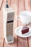 Vintage mobile phone with cup Royalty Free Stock Photos