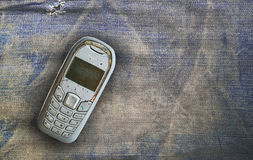 Vintage mobile phone put on old denim background Royalty Free Stock Images