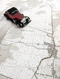 Vintage model car and map. Concept for travel planning - A photograph of a old antique toy car taken with a road travel map.  Vertical format photo.  Travel and Royalty Free Stock Image