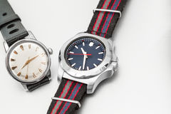 A vintage and modern watch. A vintage white dial steel watch lies diagonally alongside a modern colourful watch with a blue dial royalty free stock image