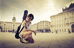 Vintage and modernity. Young woman kneeling on a town square with a guitar case on her shoulders stock images