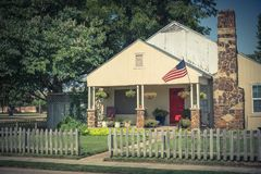 Modest home proudly displaying American flag and hanging flower royalty free stock photography