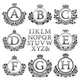 Vintage monogram kit. Black patterned letters and floral coat of arms frames for creating initial logo in antique style.  Stock Images