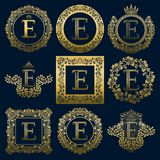 Vintage monograms set of E letter. Golden heraldic logos in wreaths, round and square frames.  Royalty Free Stock Image